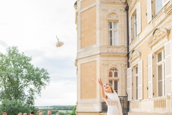 Bride throws her bouquet outside Chateau d'Azy
