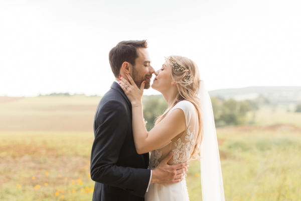 Bride and groom kiss after their elegant wedding at Chateau d'Azy in the fields