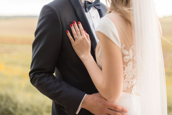 Bride with red manicure rests her hand on grooms chest in tuxedo