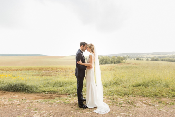 Bride and groom stand face to face in front of the field in the grounds of Chateau d'Azy