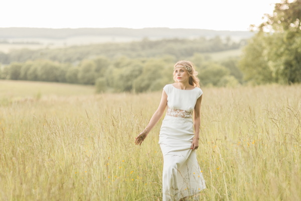 Bride walks through the fields in the grounds of Chateau d'Azy