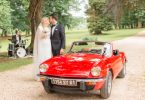 Bride and Groom kiss next to red convertible car at their Wedding at Chateau d'Azy