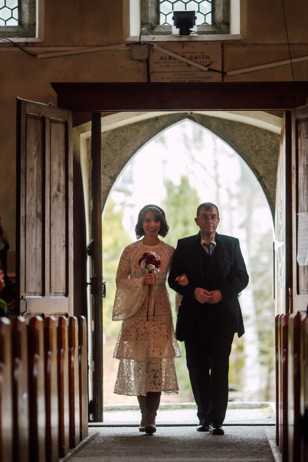 Bride and father walk into dark wooden church doors to come down aisle
