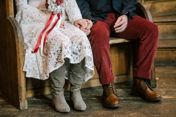 Bride and grooms legs showing grey brides boots and brown grooms boots