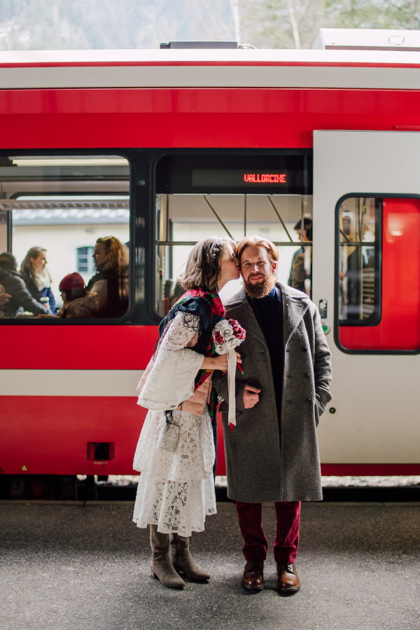 Bride and Groom kiss in front of red and white train on way to wedding