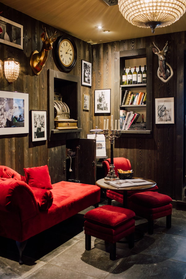 Interior of French chalet wedding venue with red plush sofas and book shelves