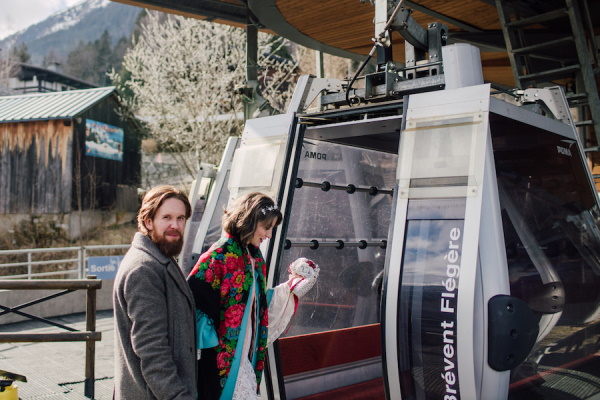 Bride and groom enter carriage of ski lift in french alps