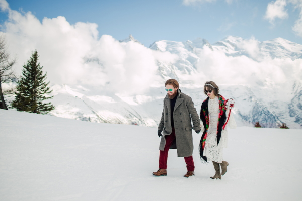 Bride and groom walk through the snow in boots in the French Alps in their suit and wedding dress