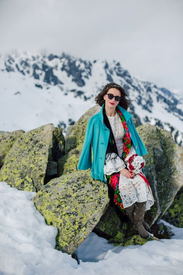 Bride in wedding dress, green woollen coat and grey boots with red lipstick sits on rocks on French Alps mountain top