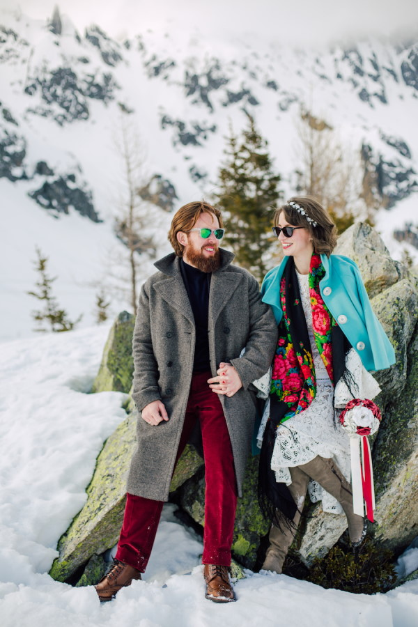 Groom in grey woollen coat ad red pants with sunglasses looks and smiles at bride in lace dress, green woollen coat and red scarf wearing sunglasses