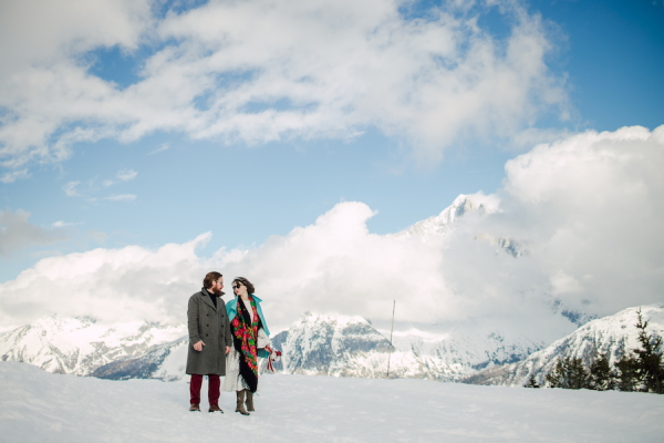 Newly married couple at the top of snowy mountain in the French Alps with snowcapped mountains behind them