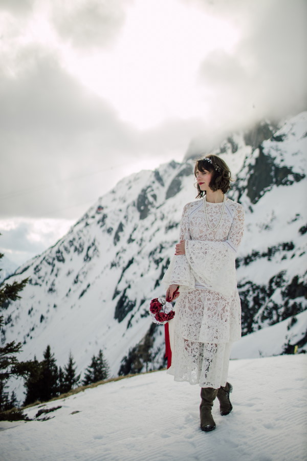 Bride in sustainable lace wedding dress with long bell sleeves and red lipstick stands in the snow in the French Alps for her Zero waste wedding