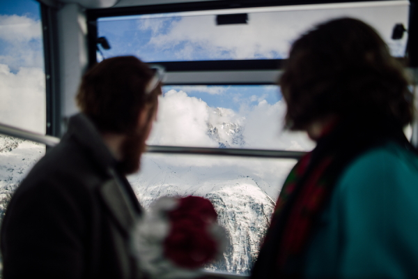 Silhouette of bride and groom looking out of ski lift at French Alps below