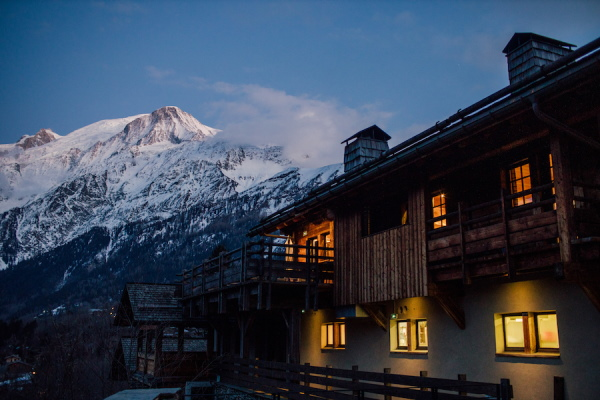 French Alps chalet in dark evening with lights and snow capped mountain in background
