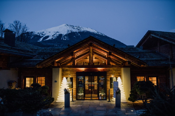 French Alps chalet in the dark with snowcapped mountain behind and bright tree-shaped lights at front entrance