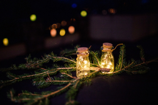 Recycled fir tree branch and small jars filled with fairy lights adorn wedding tables