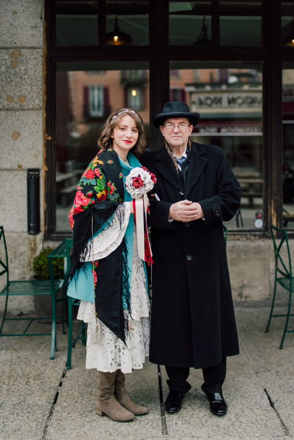 Bride in white lace dress with shawl and boots and bride's father in black woollen coat and top hat outside Brasserie and Bar