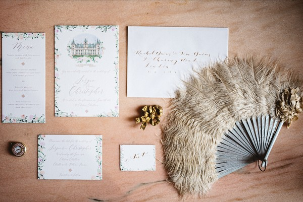 flat lay on wooden table including cream feather fan and cream and floral wedding stationery