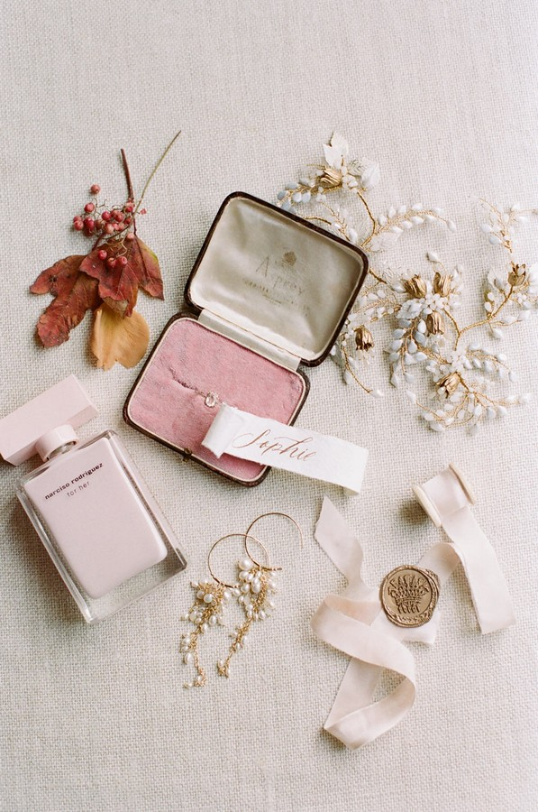 flat lay of wedding ring, narciso rodriguez perfume and pearl earrings