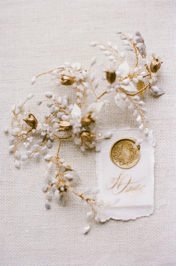 flat lay of gold and white floral hairpiece and gold wax seal on torn paper