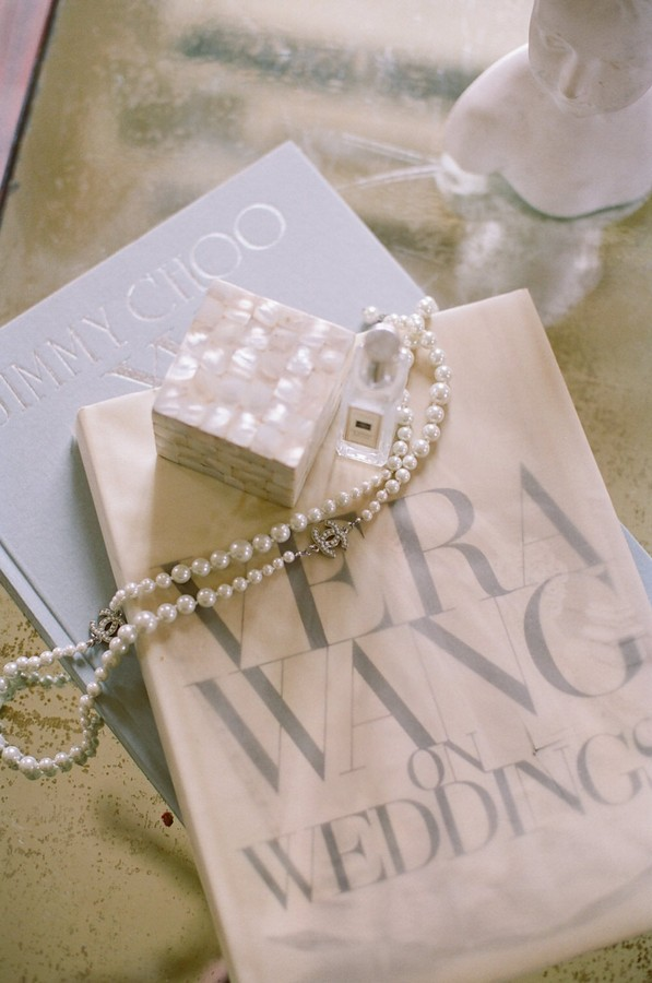 "flat lay of Vera Wang ""On Weddings"" book and pearl necklace"