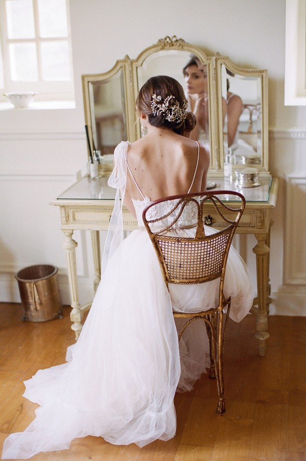 back of bride putting her earrings on in mirror of dressing table