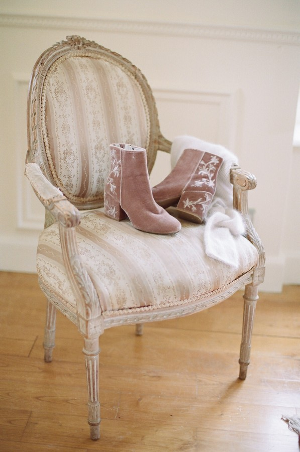 pink suede boots with floral embroidery sit on gold and cream ornate chair
