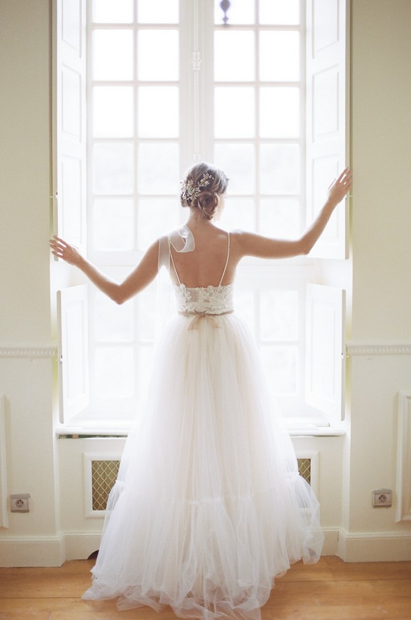 bride with arms outstretched and back to camera stands in french window frame
