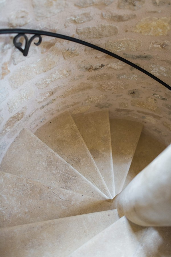 stone spiral staircase with black iron hand railing