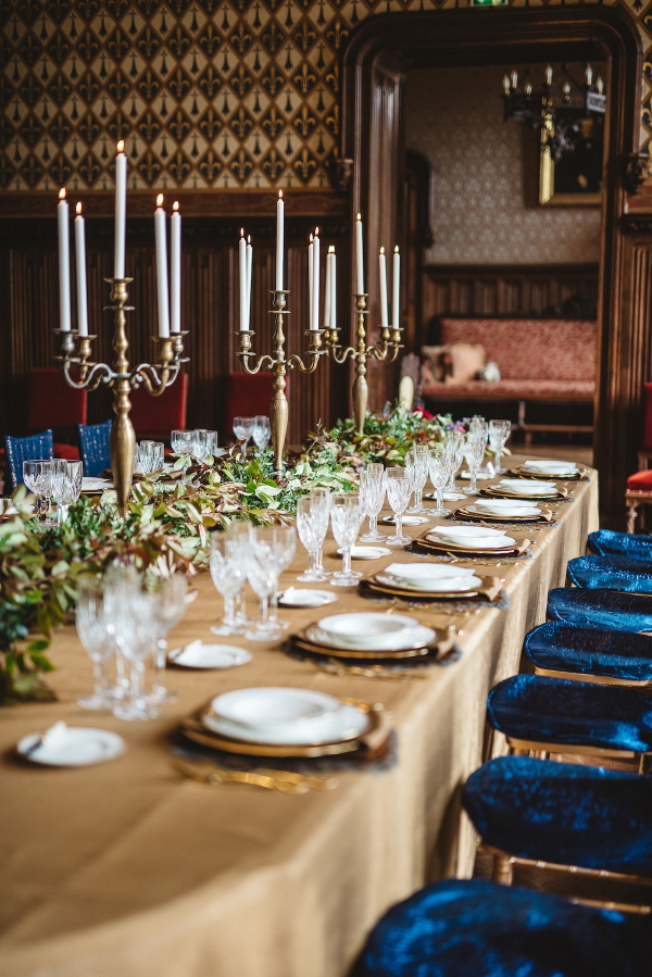 royal blue and gold wedding table setting inside chateau challain with candelabras
