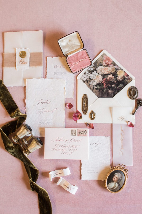 flatlay of wedding stationery, pink ring box, cameo and binoculars on pink fabric background