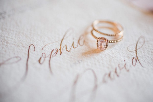 """set of gold rings with pink stone sits on wedding stationery that reads """"Sophie and David"""""""