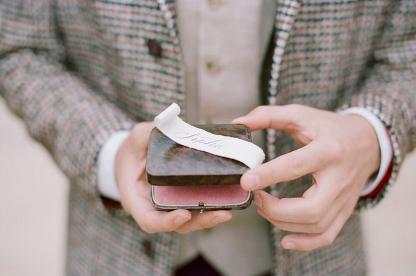 grooms hands holding ring box