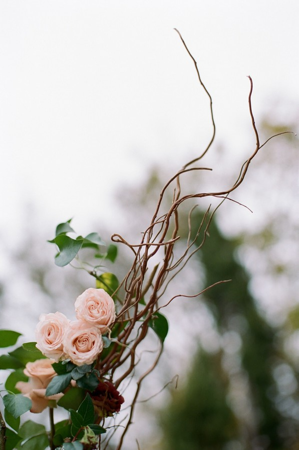 floral detail of wedding arch with brown decorative twigs