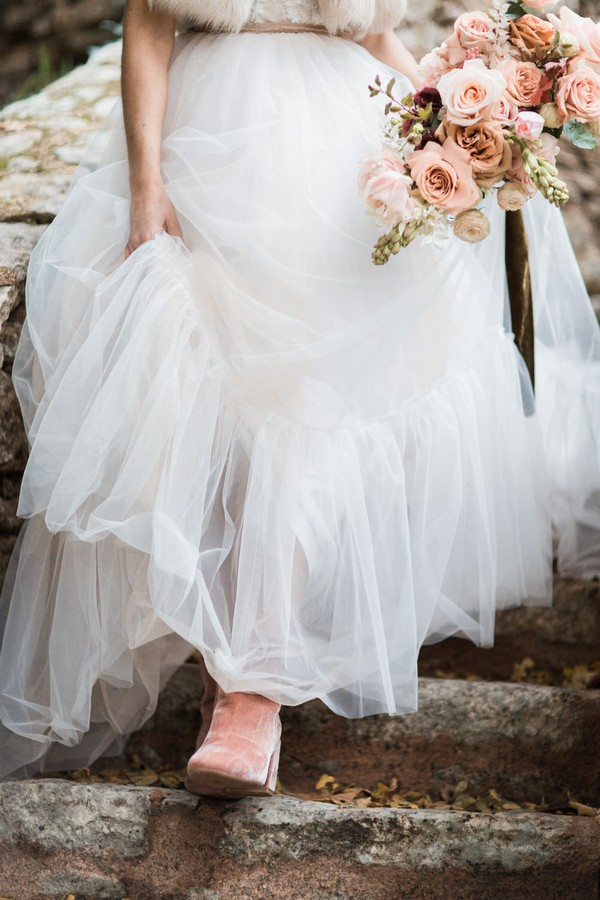 bride walking down stairs holds her dress up to reveal pink suede boots