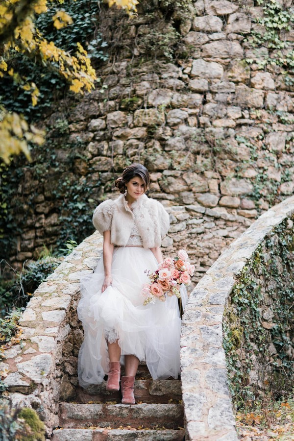 bride descends stone garden steps in angora jacket and pink suede boots under wedding dress