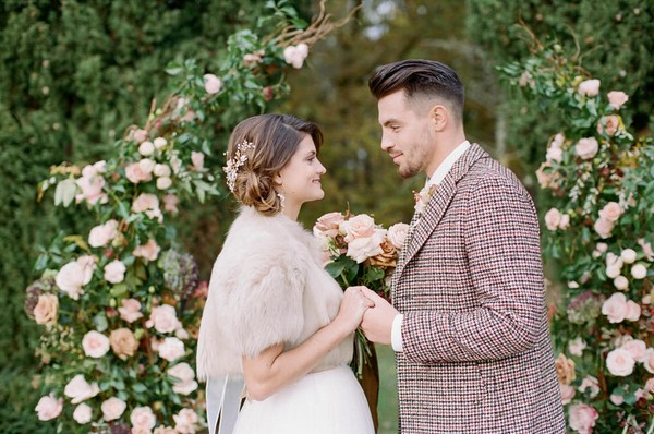 bride and groom hold hands in front of floral arch
