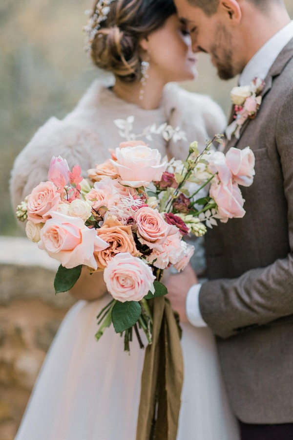 bride and groom kiss and hold pink bouquet close to camera