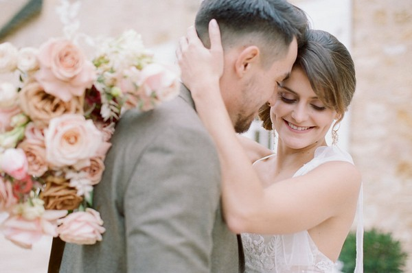 bride and groom embrace and hold pink bouquet