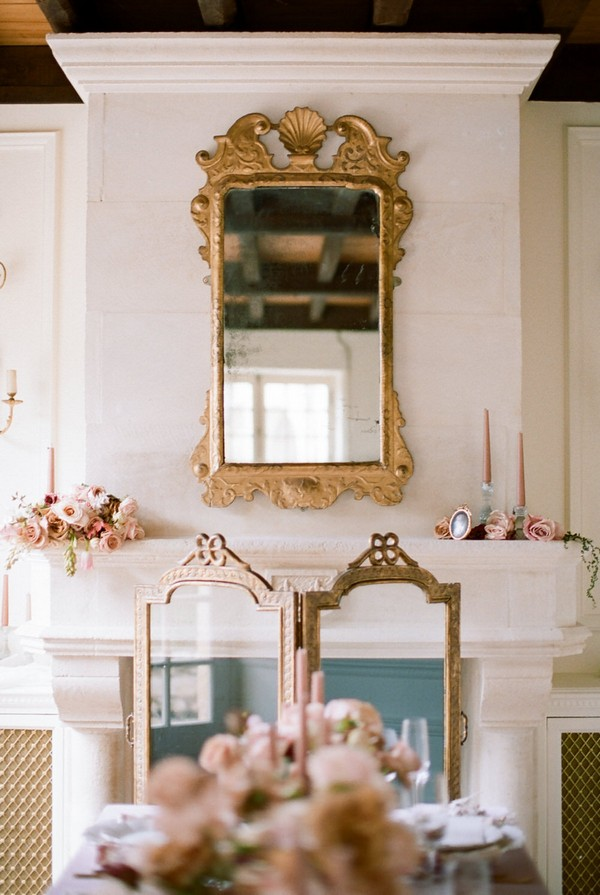 gold gilt mirror hangs above fireplace