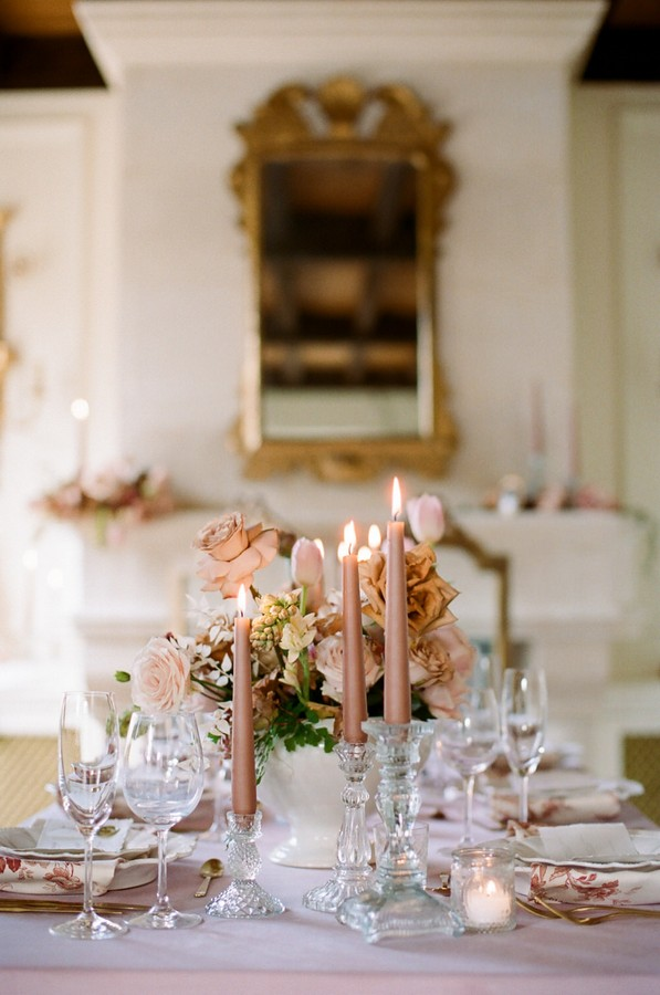 pink lit candles and crystal glassware on wedding table