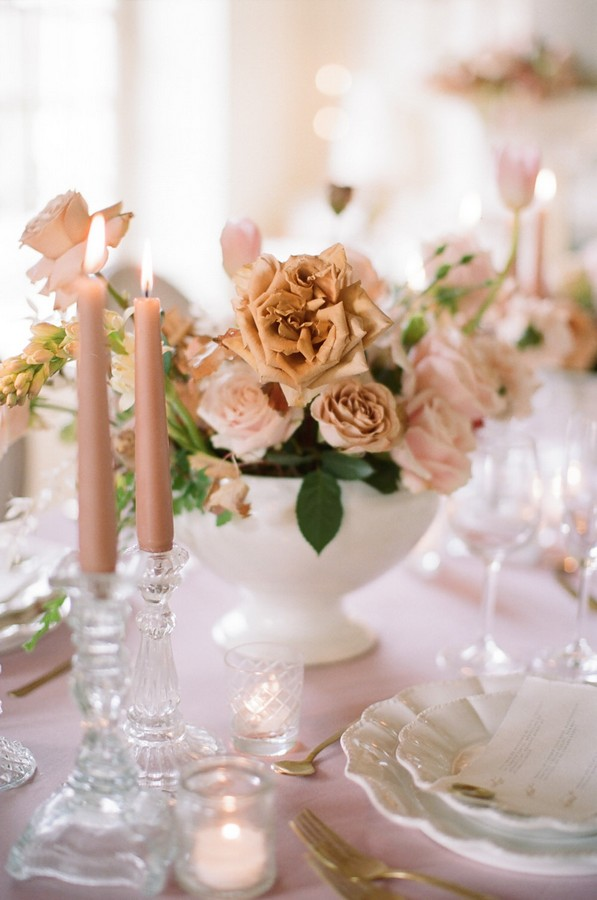pink lit candles and pink and coffee coloured floral arrangement on wedding table