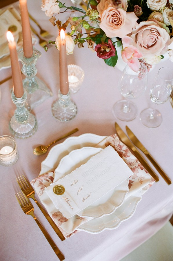 wedding stationery on white scalloped plate with gold cutlery