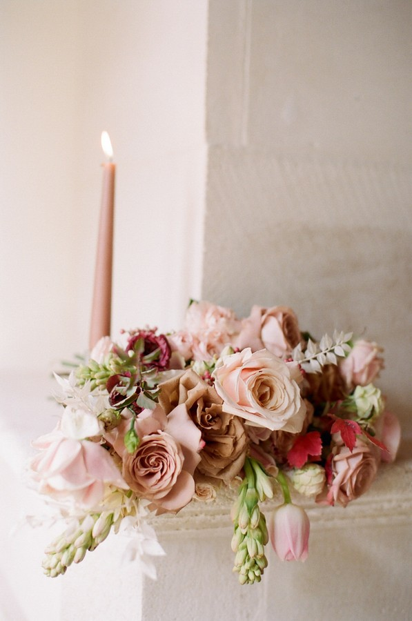 pink, coffee and burgundy coloured bouquet next to pink lit candle