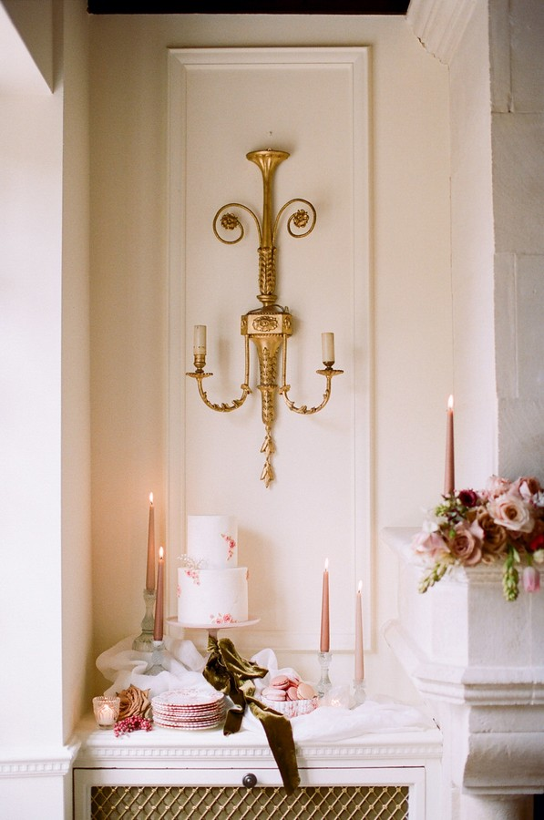 golden sconce above white and pink wedding cake