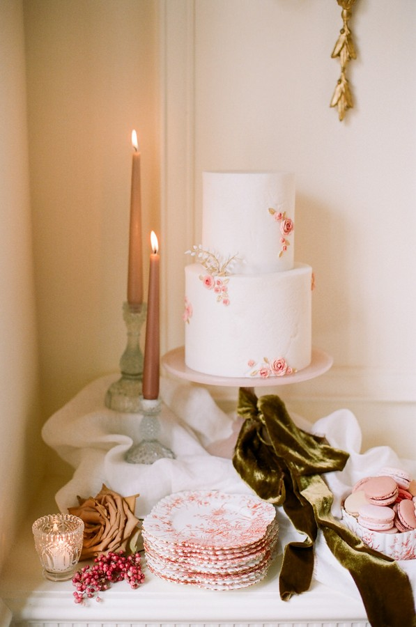 white 2 tier buttercream wedding cake with small pink flower details