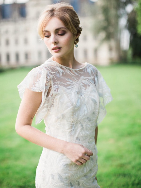 bride in cap sleeved sheer bridal gown and pearl earrings