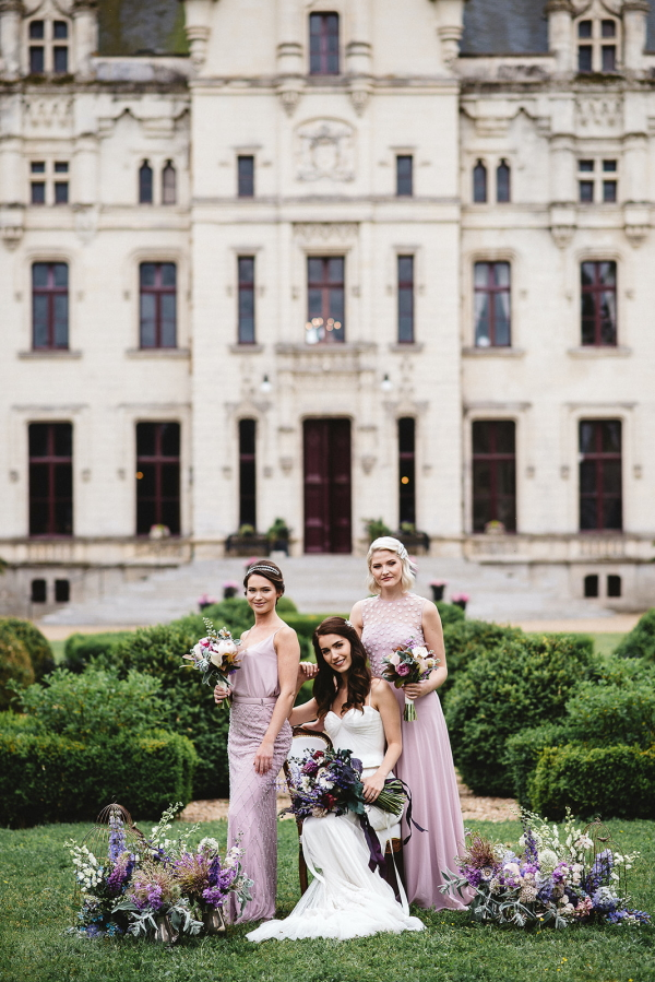 bride seated and 2 bridesmaids standing next to her in purple in front of chateau challain surrounded by purple flowers