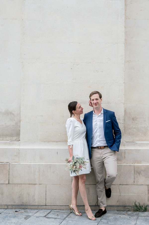 Bride in short white dress and gold shoes fixes hair of groom in blue jacket