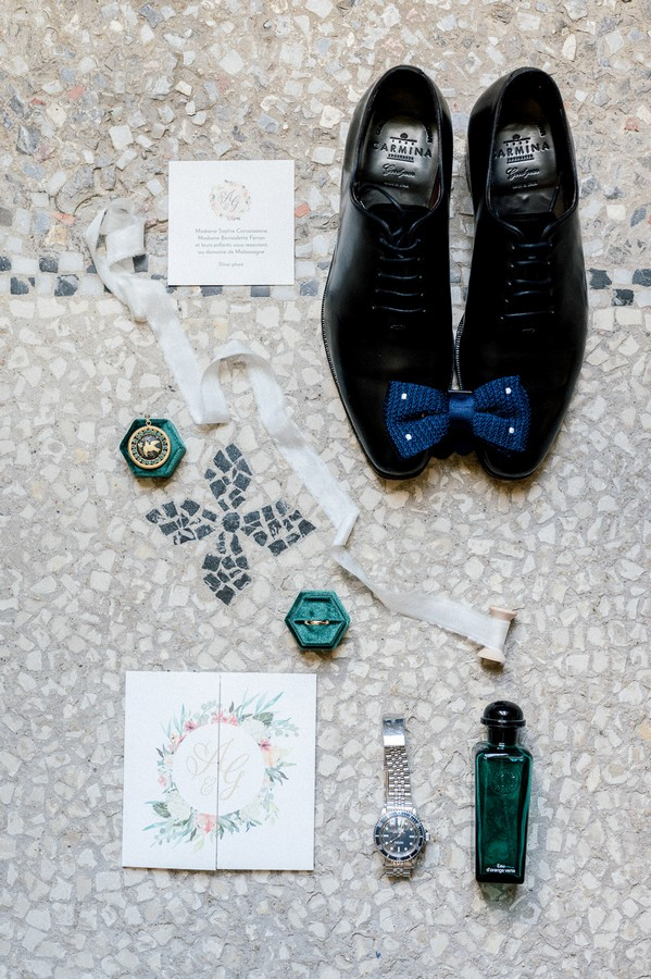 Flat lay of grooms shoes, blue bow tie, rolex and cologne